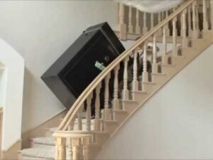 picture of gun safe being rolled upstairs from basement